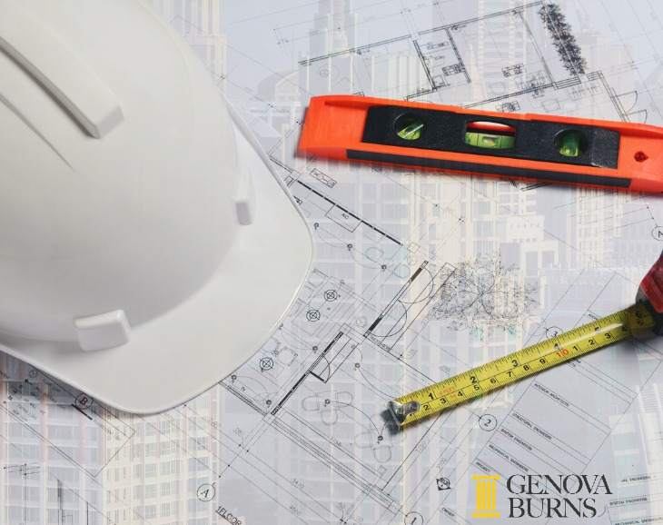 Hard hat, level and measuring tape on building plans