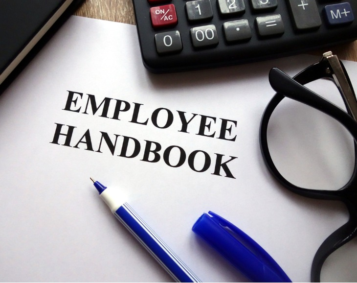 Employee handbook written on paper with pen, glasses and calculator pictured
